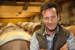 Smiling winemaker in wine cellar Royalty Free Stock Images