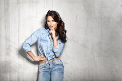 Smiling winking girl in jeans fooling around. Curly brunette smiling winking girl in jeans fooling around on gray cement background Royalty Free Stock Images
