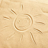 Smiling winking happy sun on golden beach sand Royalty Free Stock Images