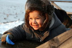 Smiling Winter Boy. Smiling 1 1/2 year old boy in winter coat and hat outdoors, , with snow on the ground beyond him stock photos