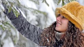 Smiling winter teen standing under pine tree with snow falling on her. Winter joy fun, Smiling winter teen standing under pine tree with snow falling on her stock video