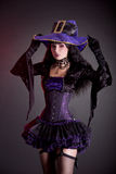 Smiling witch in purple and black gothic Halloween costume. Studio shot on black background royalty free stock photo