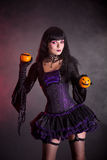 Smiling witch in purple gothic Halloween costume. Holding Jack-o-lantern style oranges stock photos