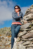 Smiling woman. A beautiful woman leaning against a stone marker atop Mount Washington Royalty Free Stock Photo