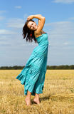Smiling woman. Wearing blue dress in the field royalty free stock images