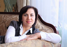 Smiling young woman has a rest on a sofa Stock Images