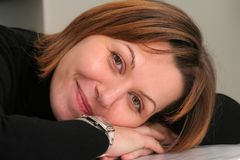 Smiling woman. Close up of smiling woman resting head on hands Stock Images