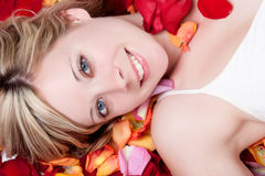 Smiling Woman. In rose petals stock photography