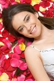 Smiling Woman. In flower petals Royalty Free Stock Images