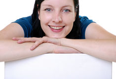 Smiling woman. Close shot of woman with head on hands leaning on white object, caucasian/white Stock Photo