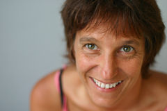 Smiling woman. A smiling middle-aged woman with green eyes stock image