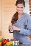 Smiling woman adding spices to her stew Royalty Free Stock Photos