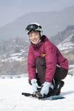Smiling Woman adjusting Ski Boot in Ski Resort Royalty Free Stock Images