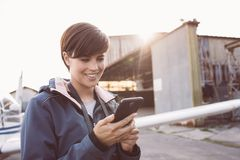 Smiling woman at the aerodrome. Smiling young woman at the aerodrome, she is connecting with her smartphone, hangar and airplane on the background stock photos