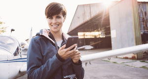 Smiling woman at the aerodrome. Smiling young woman at the aerodrome, she is connecting with her smartphone, hangar and airplane on the background royalty free stock image