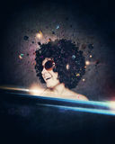 Smiling woman with afro hair listen to music with headphones. Over dark blue background Stock Image
