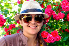 Smiling Woman Against Pretty Red Flower Plant. Close up Young Woman Wearing Hat and Sunglasses, Smiling at the Camera Against Pretty Red Flower Plant Royalty Free Stock Images