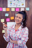 Smiling woman against wooden wall with notes on it Stock Photos