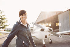 Smiling woman at the airport with light aircraft. Smiling cheerful woman posing at the airport with light aircraft and hangar on the background, she is a young royalty free stock images