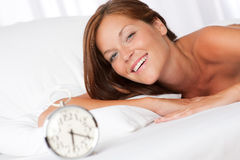 Smiling woman with alarm clock Royalty Free Stock Photo