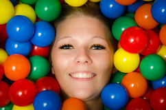 Smiling woman amongst colourful balls Stock Photos
