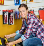 Smiling Woman Analyzing Tool Case In Store Stock Photography