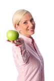 Smiling woman with an apple. A cute woman with blonde hair in her 20s, standing against a white background in a pink shirt feeling great and confident. Holding a Royalty Free Stock Photo