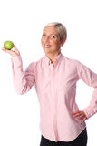 Smiling woman with an apple. A cute woman with blonde hair in her 20s, standing against a white background in a pink shirt feeling great and confident. Holding a Stock Photography