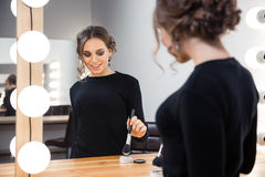 Smiling woman applying cosmetic with brush stock image