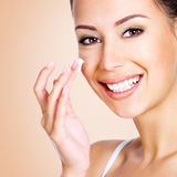 Smiling woman applying cosmetic cream Stock Photo