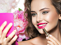 Smiling Woman applying lipstick looking at mirror stock photos