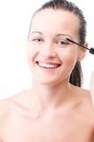 Smiling woman is applying mascara Royalty Free Stock Photos