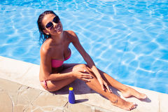 Smiling woman applying sun cream Stock Photos