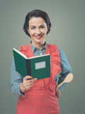 Smiling woman in apron with cookbook Royalty Free Stock Photos