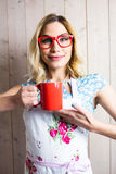 Smiling woman in apron holding a coffee mug against texture background Stock Image