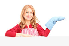 Smiling woman in apron posing with a cooking mitten. Behind a panel isolated on white background royalty free stock image