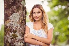 Smiling woman with arms crossed standing by tree Royalty Free Stock Images