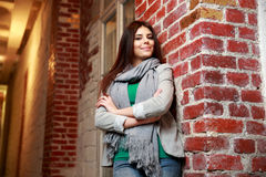 Smiling woman with arms folded leaning on the brick wall Royalty Free Stock Image