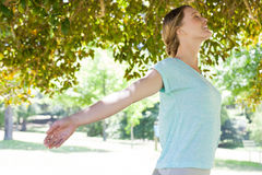 Smiling woman with arms outstretched at park Royalty Free Stock Photo