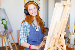 Smiling woman artist painting on canvas and listening to music. Charming smiling young woman artist in headphones and apron painting on canvas and listening to royalty free stock photo