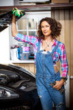 Smiling woman as a mechanic in a garage. Rare professions for female. car is being repaired in the workshop Stock Photography