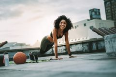 Fitness woman doing push ups on rooftop. Smiling woman athlete doing push ups on the rooftop with gym balls by her side. Cheerful woman in fitness wear doing stock photography