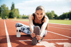Smiling woman athlete stretching legs on stadium Stock Images