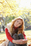 Smiling woman in autumn golden park Royalty Free Stock Image