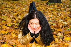 Smiling woman on autumn leaves Royalty Free Stock Image