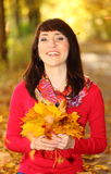 Smiling woman in autumn park with leaves in hands Royalty Free Stock Images