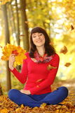 Smiling woman in autumn park with leaves in hands Royalty Free Stock Photo
