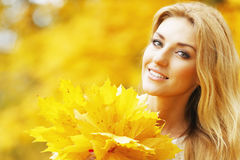Smiling woman in autumn park Stock Photo