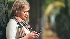 Smiling woman in autumn park typing message on the mobile phone stock video footage