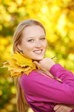 Smiling woman at autumn. Young smiling woman with autumn maple leaves in park at fall outdoors stock photos